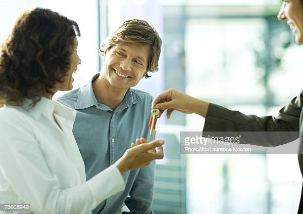 Couple smiling at each other as woman accepts keys from second woman