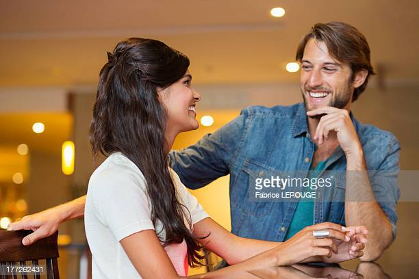 Couple smiling at each other in a bar