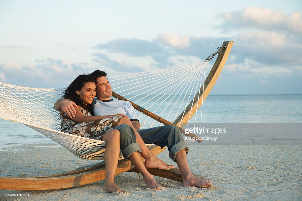 Couple smiling in hammock on beach, side view