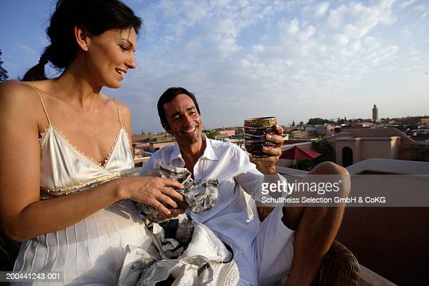 Couple smiling, man holding up bowls, outdoors