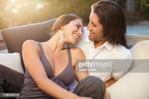 couple smiling on pool lounge chair with sunset : Stock Photo