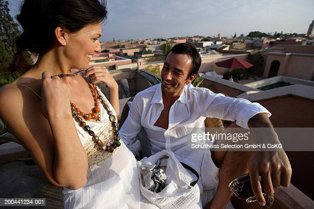 Couple smiling, woman holding up necklace