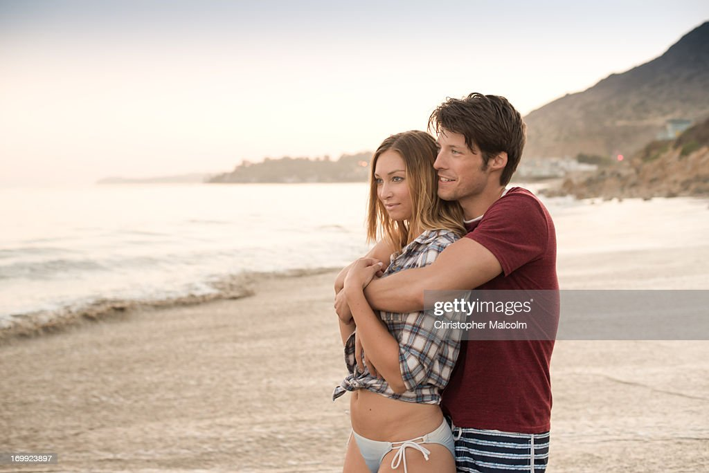 Couple snuggling on beach : Stock Photo