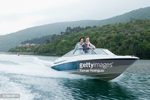 Couple speeding on motorboat : Bildbanksbilder