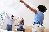 Couple Spreading Bedsheet Over Son