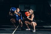 Young athletic man and woman squatting with weighted balls at gym