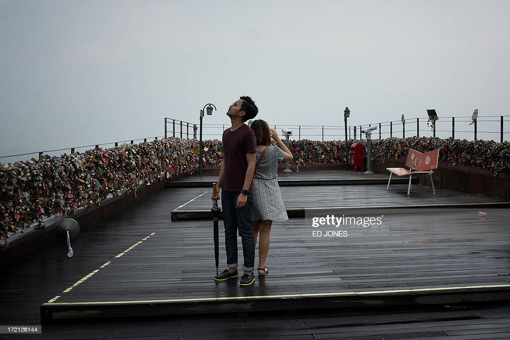 A couple stand at a viewpoint overlooking the Seoul city skyline during rainfall on July 2, 2013. July marks the wet season for Seoul during which the city of10 million people receives some 60 percent of its annual rainfall. AFP PHOTO / Ed Jones