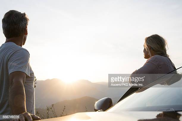 Couple stand by car door, look to sunrise, hills