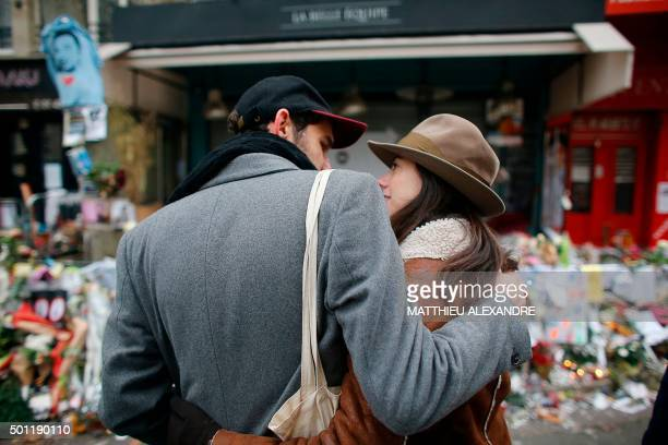 A couple stand in front of a makeshift memorial in front of the cafe 'La Belle Equipe' on rue de Charonne in Paris' 11th arrondissement in Paris on...