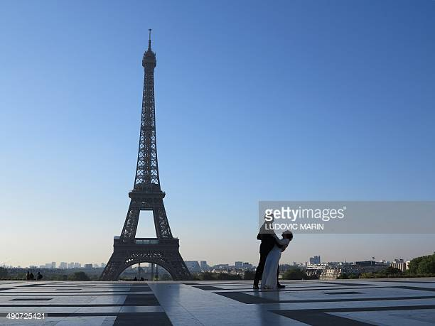 A couple stand in front of the Eiffel Tower in the morning on May 15 2014 in Paris MARIN