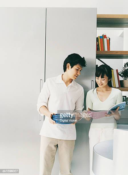 Couple Stand Looking at a Magazine in Their Living Room
