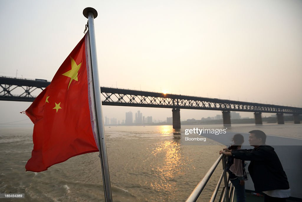 A couple stand near a Chinese national flag on a ferry crossing the Chang Jiang river in Wuhan, China, on Sunday, Oct. 20, 2013. China's economic expansion accelerated to 7.8 percent in the third quarter from a year earlier, the statistics bureau said Oct. 18, reversing a slowdown that put the government at risk of missing its 7.5 percent growth target for 2013. Photographer: Tomohiro Ohsumi/Bloomberg via Getty Images