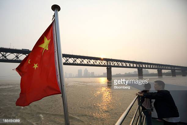 A couple stand near a Chinese national flag on a ferry crossing the Chang Jiang river in Wuhan China on Sunday Oct 20 2013 China's economic expansion...