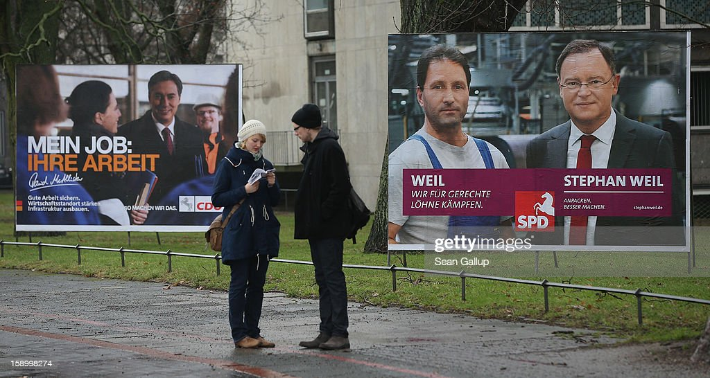 A couple stand near election campaign billboards featuring Hanover Mayor and German Social Democrats (SPD) candidate Stephan Weil (R) and Lower Saxony Governor and incumbent candidate of the German Christian Democrats (CDU) David McAllister on January 5, 2013 in Hanover, Germany. Lower Saxony is holding state elections on January 20 and many analysts see the election as a bellwether for national elections scheduled to take place later this year.