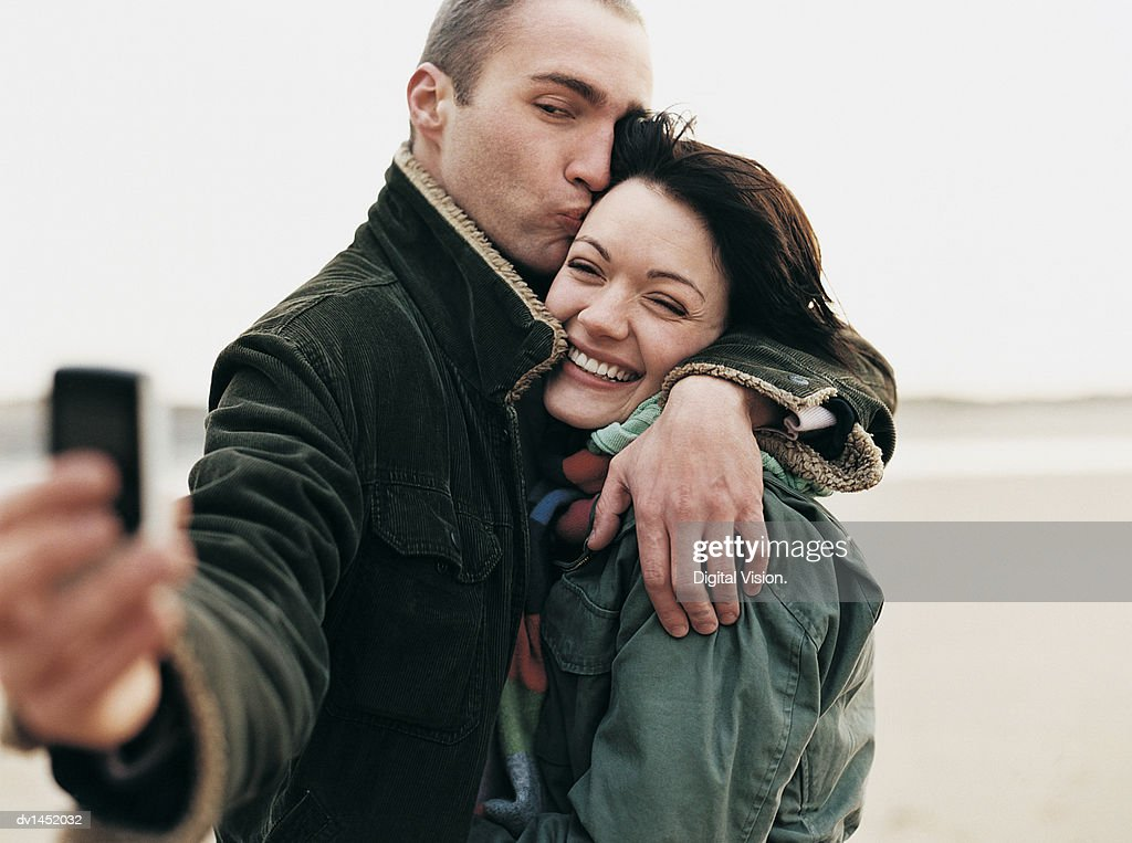 Couple Stand on a Beach Taking a Self-Portrait : Stock Photo