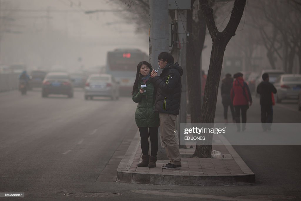 A couple stand on a roadside during severe pollution in Beijing on January 12, 2013. Air quality data released via the US embassy twitter feed recorded air quality index levels so hazardous that they were classed as 'Beyond Index'. By 4pm the particle matter (PM) 2.5 figure was 728 on a scale that stops at 500 at which point the US embassy website advises against all outdoor activity. AFP PHOTO / Ed Jones