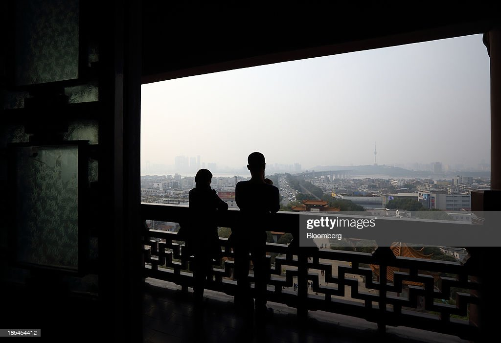 A couple stand on an observation deck at the Yellow Crane Tower in Wuhan, China, on Sunday, Oct. 20, 2013. China's economic expansion accelerated to 7.8 percent in the third quarter from a year earlier, the statistics bureau said Oct. 18, reversing a slowdown that put the government at risk of missing its 7.5 percent growth target for 2013. Photographer: Tomohiro Ohsumi/Bloomberg via Getty Images