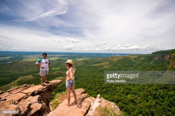 A couple stand on an outcrop and enjoy the view of the Chapada dos Guimaraes on November 17 2013 near Cuiaba Brazil The area is constituted as a...