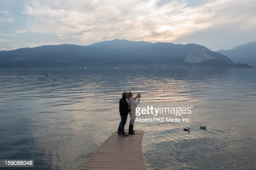 Couple stand on curving lake pier, take picture : Stock Photo