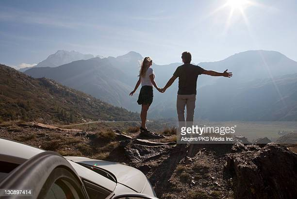 Couple stand on mtn ridge by car, arms outstrethed
