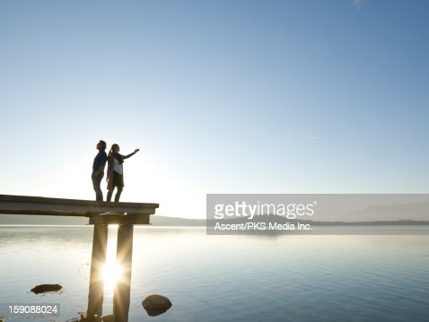 Couple stand on pier above mtn lake, take picture : Stock Photo