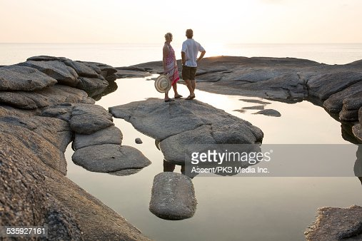 Couple stand on rock island, look out to sea, sun : Stock Photo