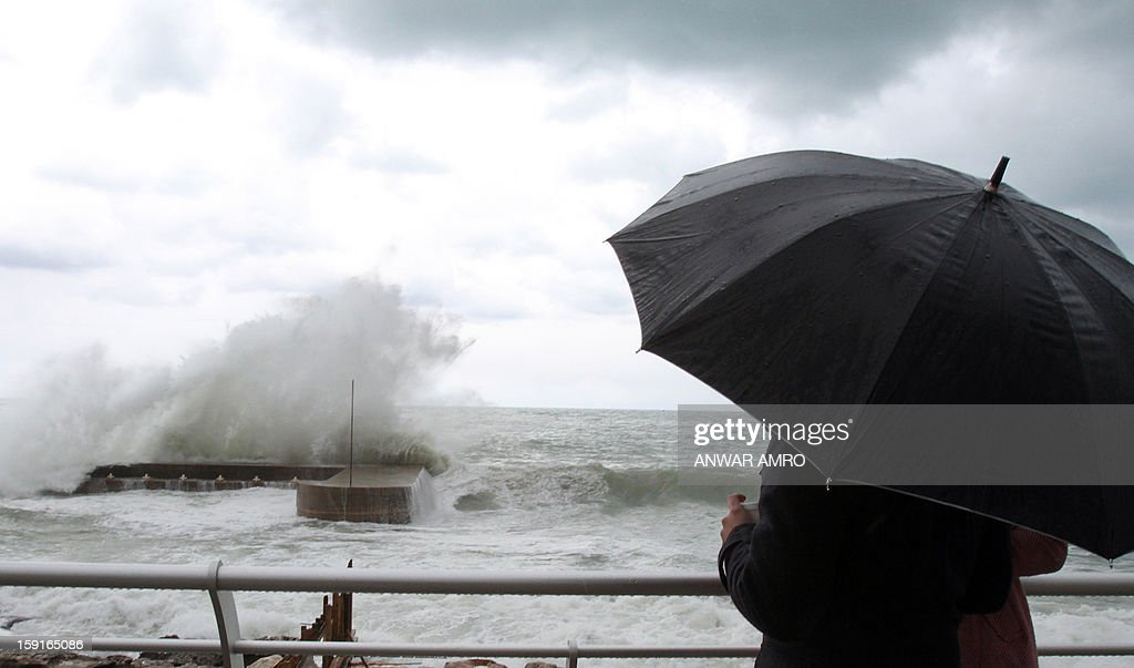 A couple stand on the promenade in Beirut and watch the waves crash against the rocks as stormy weather conditions continues in Lebanon on January 9, 2013. A met office official at Beirut airport said the storm and lower temperatures would result in snowfall in the mountains as low as 300 metres (1,000 feet).