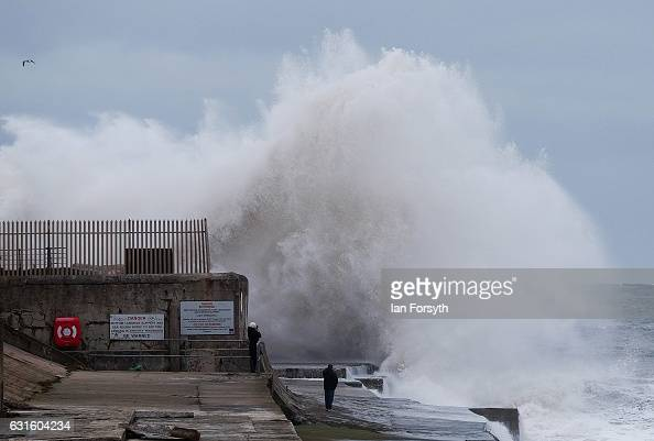 A couple stand on the sea wall as huge waves crash over the lighthouse at an area known as South Gare on January 13 2017 in Redcar United Kingdom The...