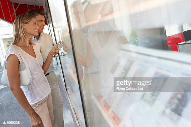 Couple Stand Outside an Estate Agents Looking at the Window Display