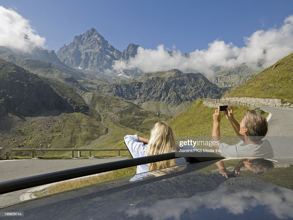 Couple stand outside of car, take picture of mtns : Stock Photo
