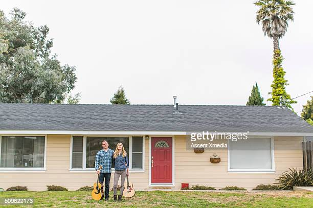 Couple stand outside of home, holding guitars