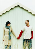 Couple Stand Side-by-Side Against a Beach Hut Holding Hands