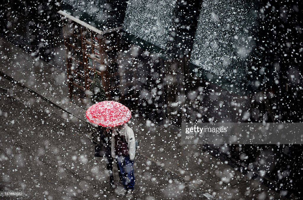 A couple stand under an umbrella during a heavy snowfall in Pristina on December 5, 2012.