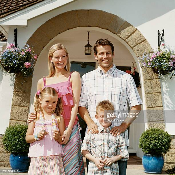 Couple Stand With Their Young Son and Daughter in Front of Their Bungalow