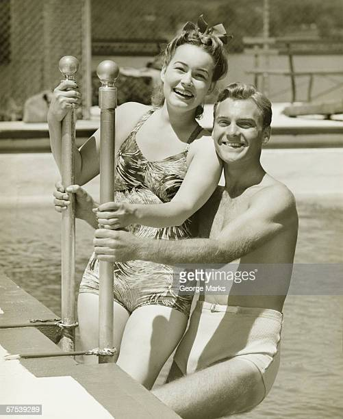 Couple standing at railings in pool, (B&W), portrait