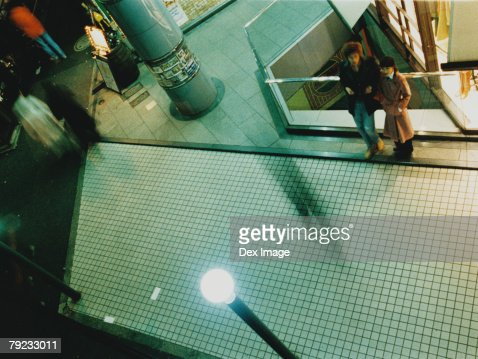 Couple standing at shopping center atrium, elevated view : Stock Photo