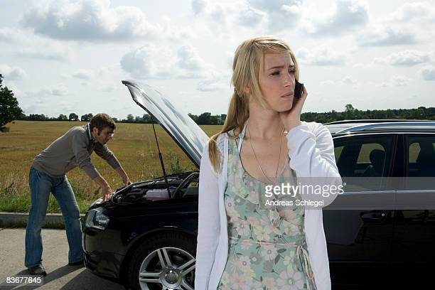 A couple standing at the roadside next to their broken down car
