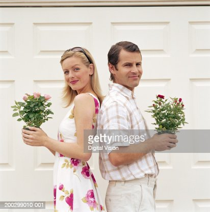 Couple standing back to back, holding potted plants, smiling, portrait : Stock-Foto