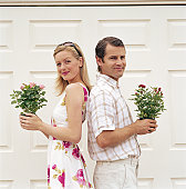Couple standing back to back, holding potted plants, smiling, portrait