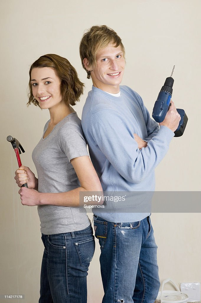 Couple standing back to back holding power tools, Cape Town, Western Cape Province, South Africa : Stock Photo