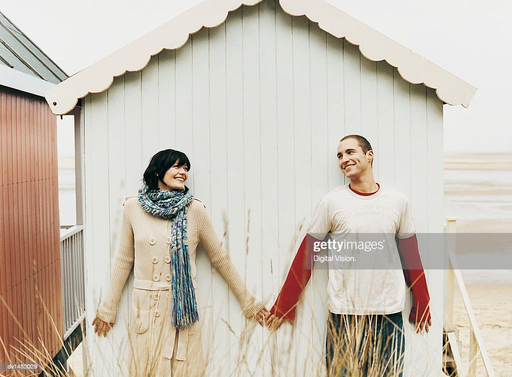 Couple Standing Behind a Beach Hut in Winter Side-by-Side and Holding Hands : Stock Photo
