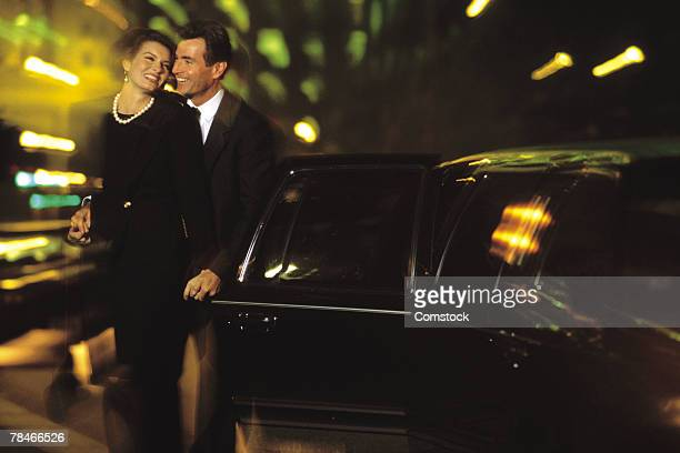 Couple standing beside a limo at night