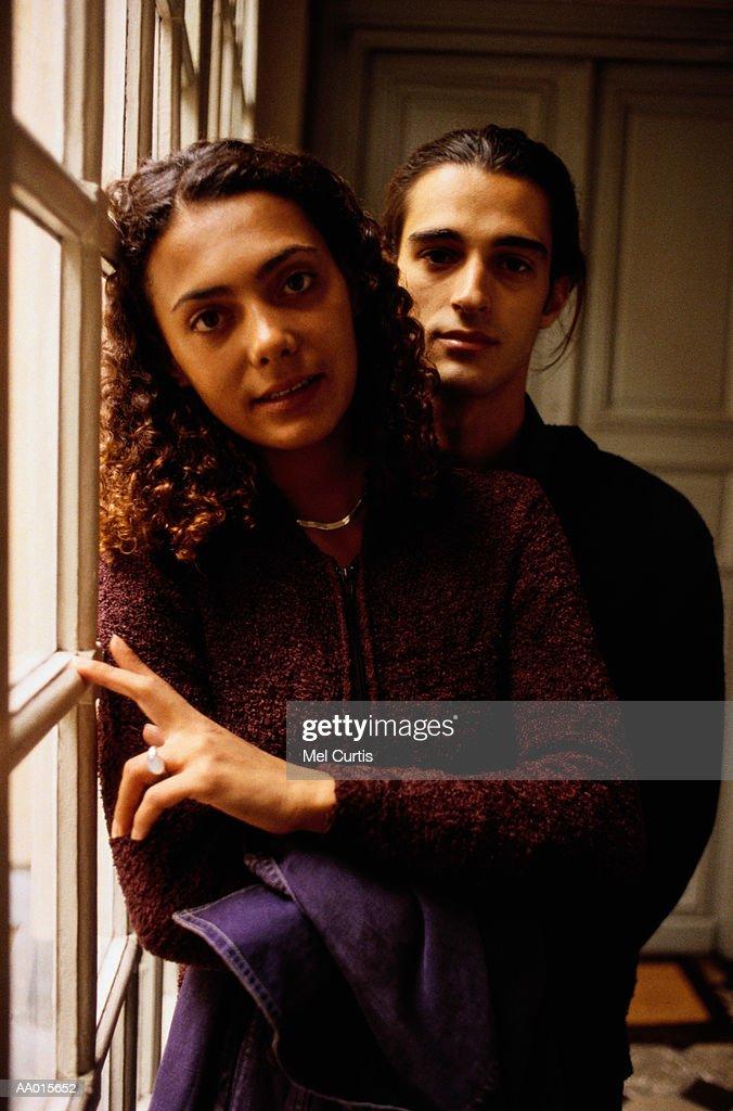 Couple Standing Beside a Window : Stock Photo