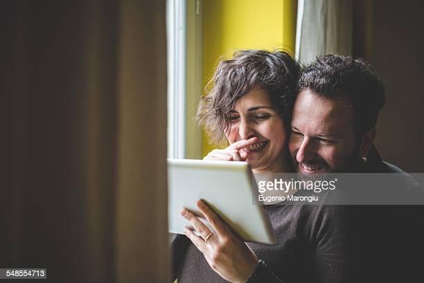 Couple standing beside window, using digital tablet