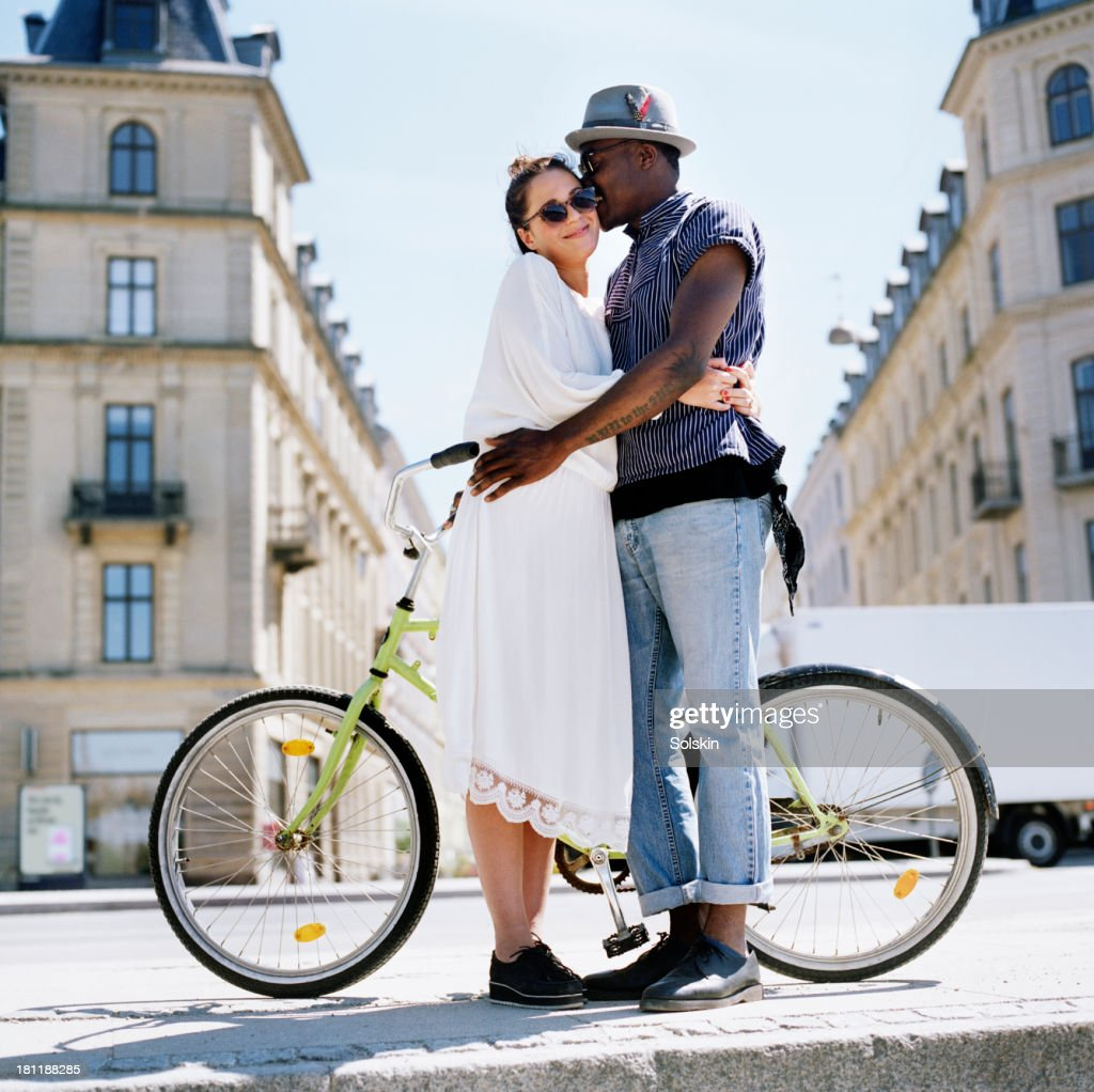 couple standing by bicycle, hugging each other