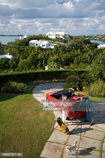 Couple standing by car on footpath in garden, elevated view