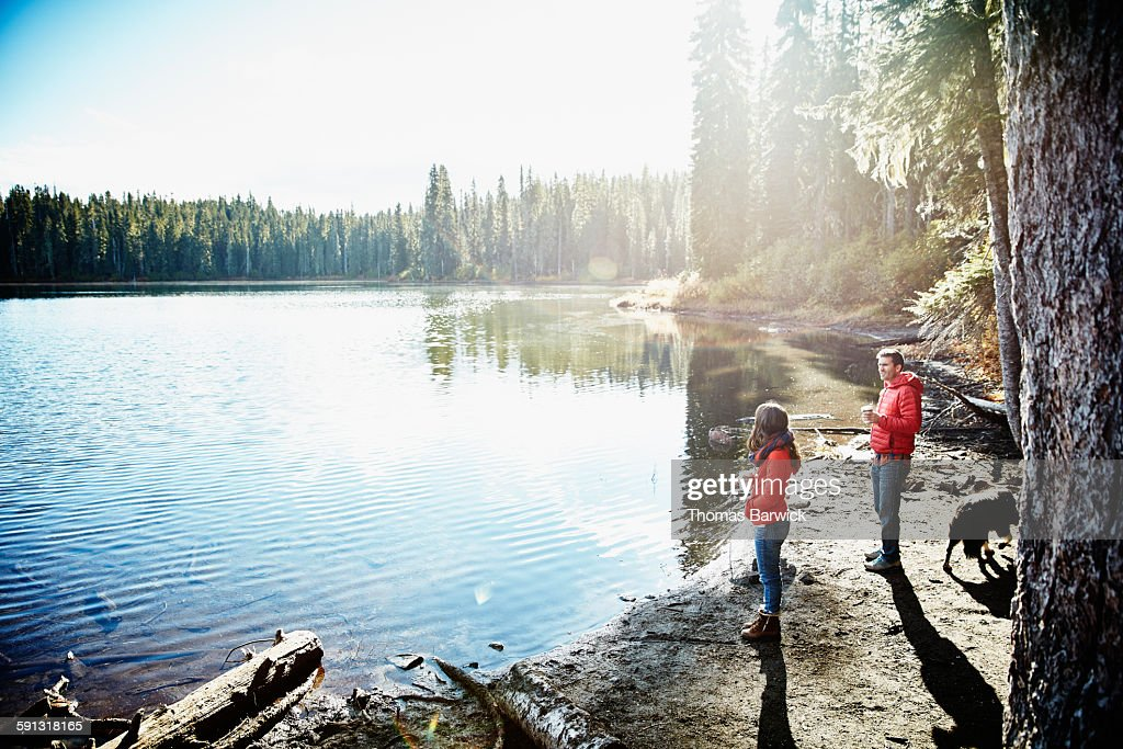 Couple standing by lake drinking coffee at sunrise