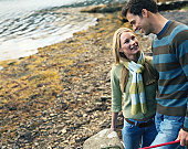 Couple standing by lake, smiling