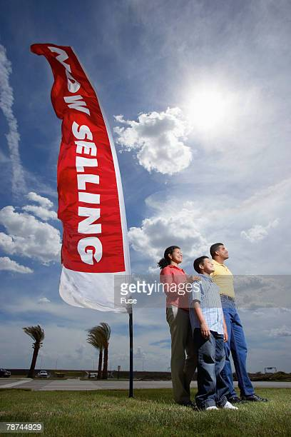 Couple Standing by Sale Sign