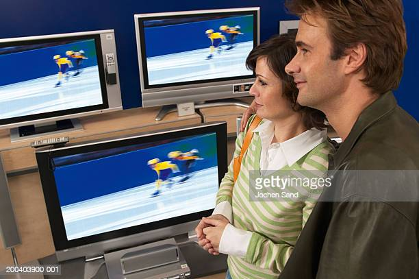 Couple standing by televisions in shop, smiling